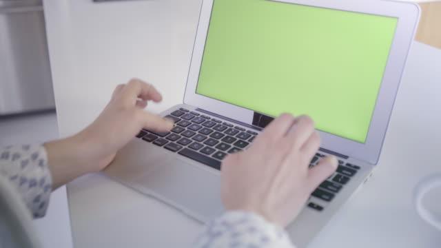 junge kaukasischen frau im ihren 30ern mit ihrem laptop mit einem grünen bildschirm, um neue inhalte einfügen - einzelne frau über 30 stock-videos und b-roll-filmmaterial