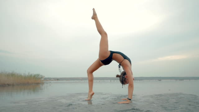 Young caucasian woman in swimsuit practicing yoga in water liman, lake or river. Beautiful reflection. Complex asanas, balance. Fitness, sport, yoga and healthy lifestyle concept. Slow motion video
