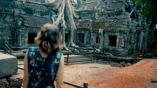 young caucasian woman   in ta prohm temple - tempio video stock e b–roll