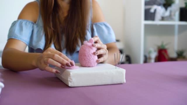 young caucasian woman making wool dry felting tutorial - feltro video stock e b–roll