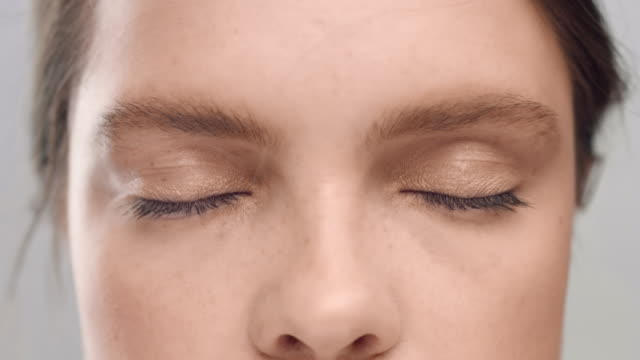 Young Caucasian woman opening her eyes in front of camera video