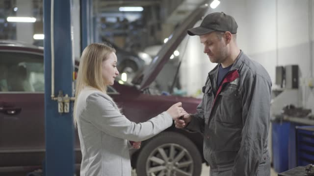 Young Caucasian woman passing car keys to maintenance engineer and shaking his hand. Positive confident lady leaving vehicle in repair shop for fixing or tuning. Service, maintening, auto industry.