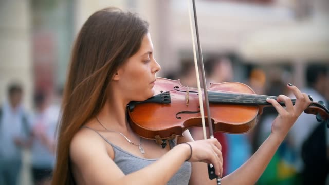 young caucasian woman playing a fiddle on pedestrian street at summer day - orchestra video stock e b–roll
