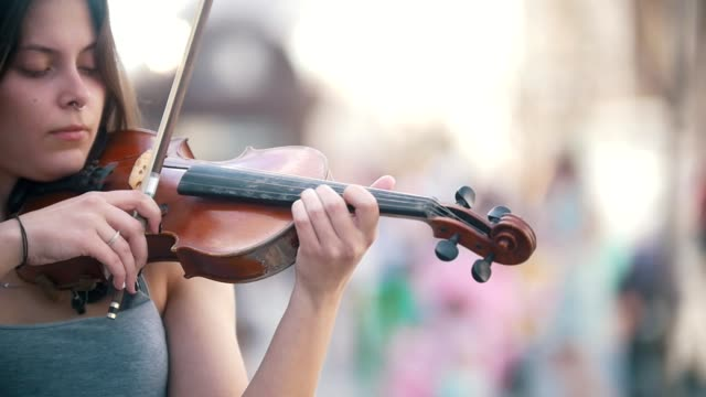 Young caucasian woman playing a fiddle on pedestrian street at summer day