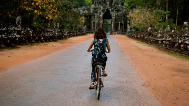 junge kaukasischen frau reiten fahrrad in angkor wat - kambodschanische kultur stock-videos und b-roll-filmmaterial