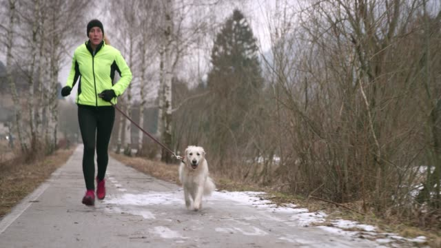 Young Caucasian woman running on a walkway in winter with her dog