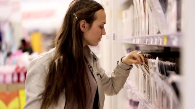 unga kaukasiska kvinna väljer en tights i köpcentret. - gympingdräkt bildbanksvideor och videomaterial från bakom kulisserna
