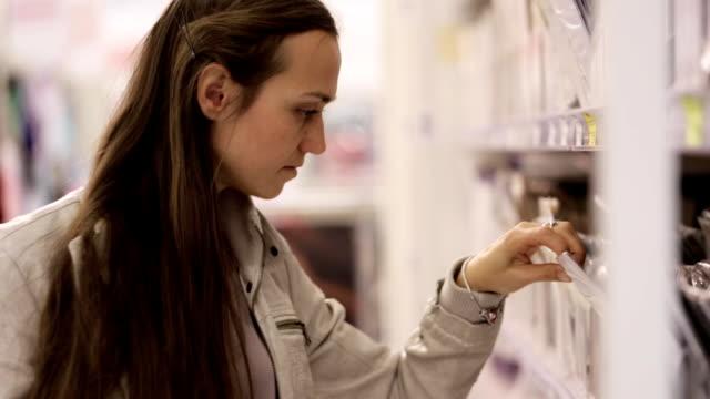 kaukasische mädchen wählt eine strumpfhose im einkaufszentrum. - gymnastikanzug stock-videos und b-roll-filmmaterial