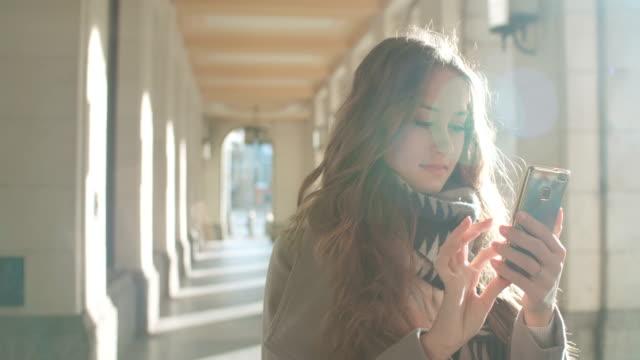 vídeos y material grabado en eventos de stock de mujer caucásica joven con teléfono en una ciudad. - moda de otoño