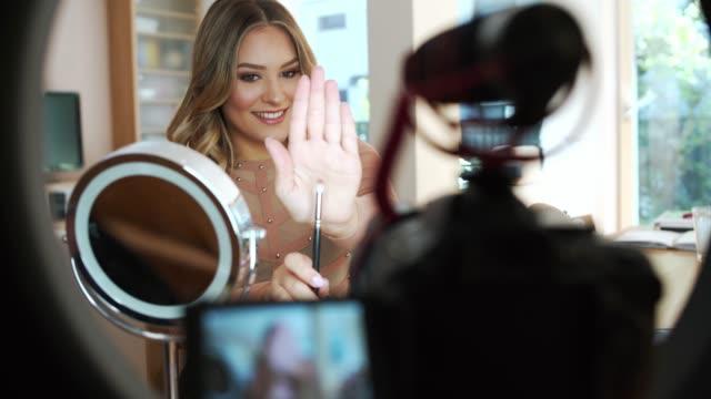 vidéos et rushes de jeune femme caucasienne vlogging au sujet du maquillage - fard à paupières