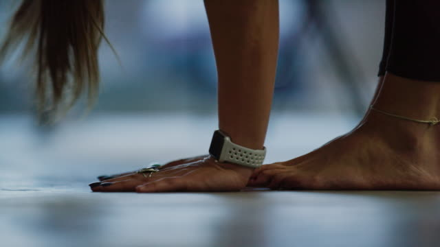 A Young Caucasian Woman with a Watch Puts Her Hands on the Floor in a Forward Bend and Then Stands Up Again in an Exercise Studio