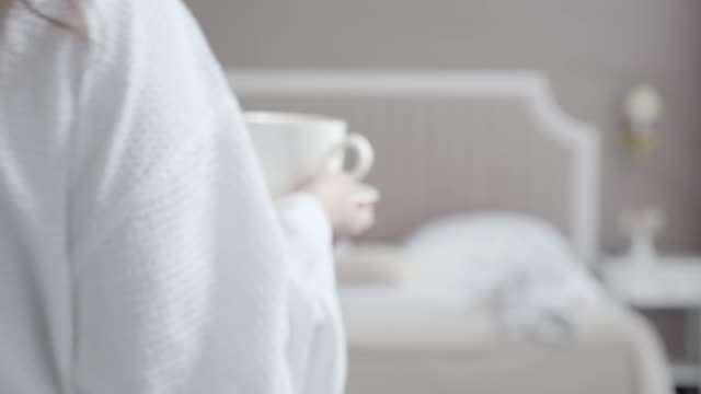 Young Caucasian woman with coffee cup in hand walking to bed and sitting down. Blurred brunette female tourist resting in hotel room in the morning. Tourism, leisure, vacations, relaxation.