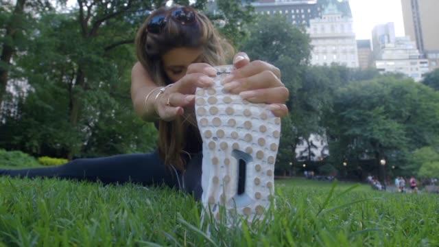 彼女が彼女の実行を開始する前に、長いブルネットの髪を持つ若い白人女性公園、ストレッチと温めで草の上に座ってください。 - 女性選手点の映像素材/bロール