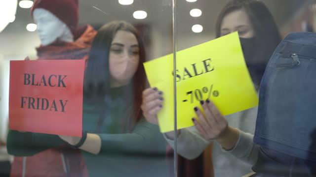 junge kaukasische frauen nähern sich schaufenster und hängen ankündigungen über schwarzen freitag verkauf. porträt von zwei verkäuferinnen in covid gesichtsmasken, die kleidung während der coronavirus-pandemie verkaufen. - black friday stock-videos und b-roll-filmmaterial