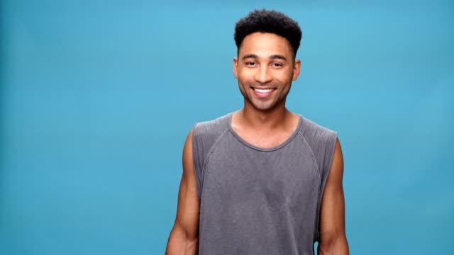 stockvideo's en b-roll-footage met jonge charmante afrikaanse man over blauwe achtergrond. - portrait background