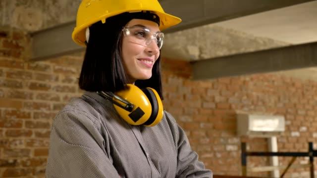 vídeos de stock e filmes b-roll de young charming architect woman looking forward, smiling and confidently nodding, smiling, brick building background - proteção