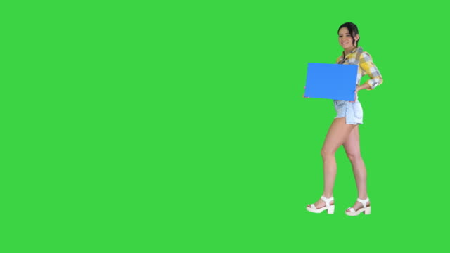 young charming brunette model holding empty board on a green screen, blue mockup - pantaloncini video stock e b–roll