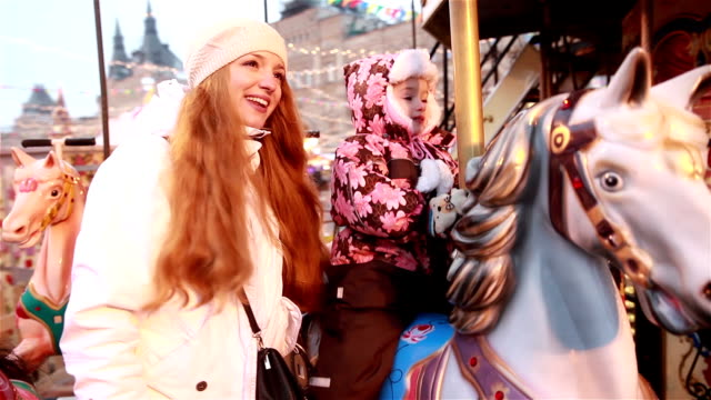 Young charming mom and her daughter ride on the carousel in the winter.