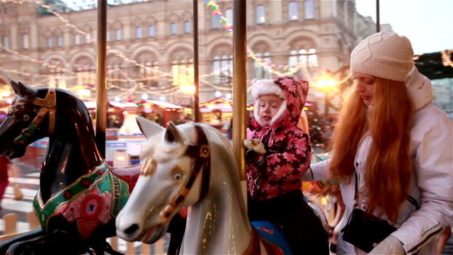 Young charming mom and her daughter ride on the carousel in the winter. video