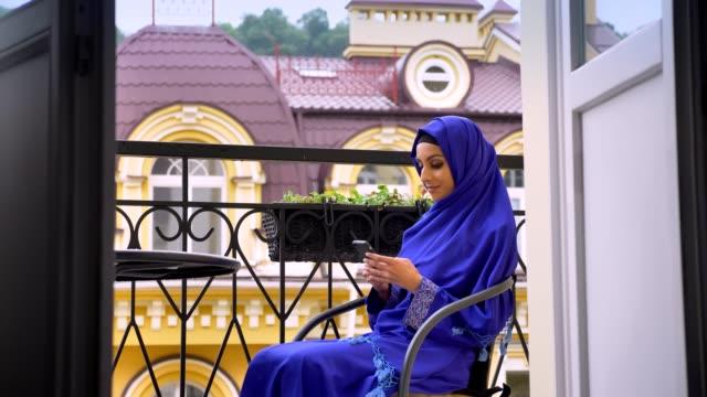 unga charmiga muslimsk kvinna i hijab som sitter i stol på balkongen och att skriva på mobilen - anständig klädsel bildbanksvideor och videomaterial från bakom kulisserna