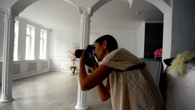 vídeos de stock, filmes e b-roll de fotógrafo de mulher encantadora jovem tirando fotos com a câmera dslr dentro de casa com quarto interior grunge - temas fotográficos