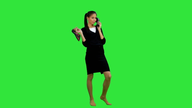 Young chatty woman using a shoe like a telephone on a Green Screen, Chroma Key video