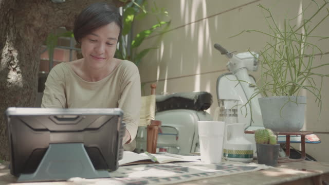 young cheerful asian woman sitting and video call meeting working on laptop. - new normal video stock e b–roll