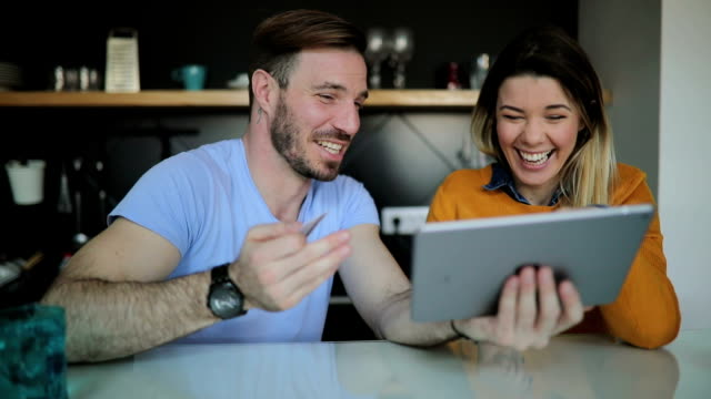 Young cheerful couple shopping online at home video