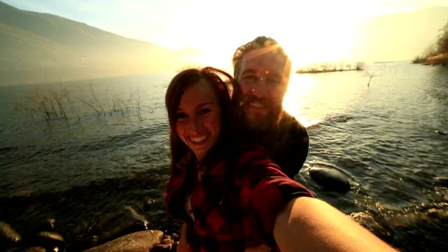 Young cheerful couple takes a selfie portrait by beautiful lake video