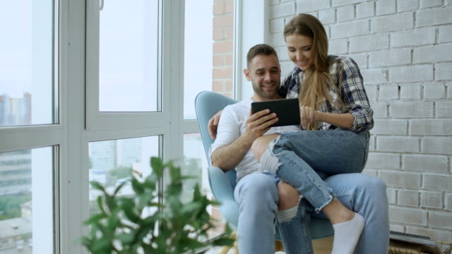 Young cheerful couple talking and using tablet computer on balcony in modern loft apartment video