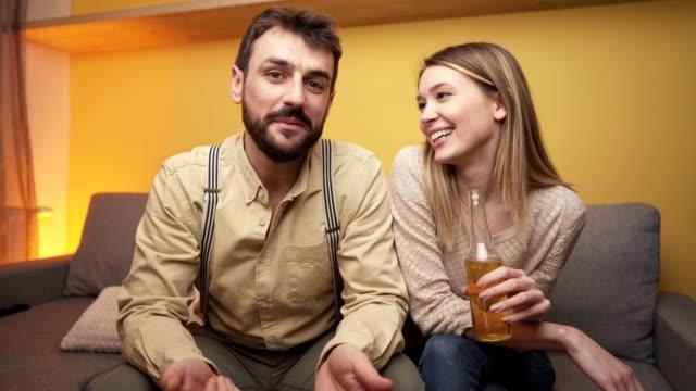自宅に座っている間にビデオ通話で話している若い陽気なカップル ビデオ