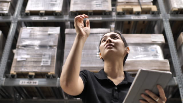 Young cheerful female worker is using her tablet in factory storage area Young cheerful female worker is using her tablet in factory storage area forklift stock videos & royalty-free footage
