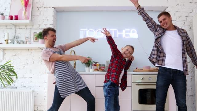 junge fröhliche schwule familie mit einem kind posiert und spaß in der küche. - gay man stock-videos und b-roll-filmmaterial