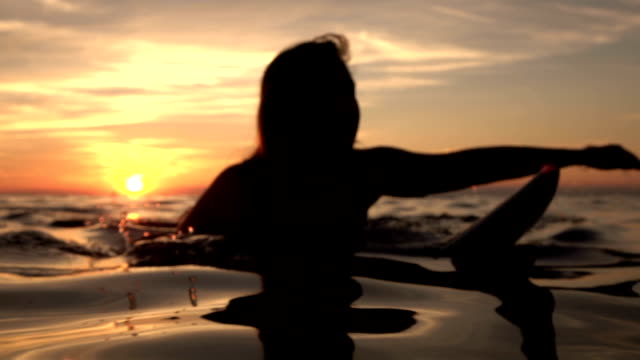 dof: young cheerful girl paddling in deep ocean on surfboard at golden sunset - pesche bambino video stock e b–roll