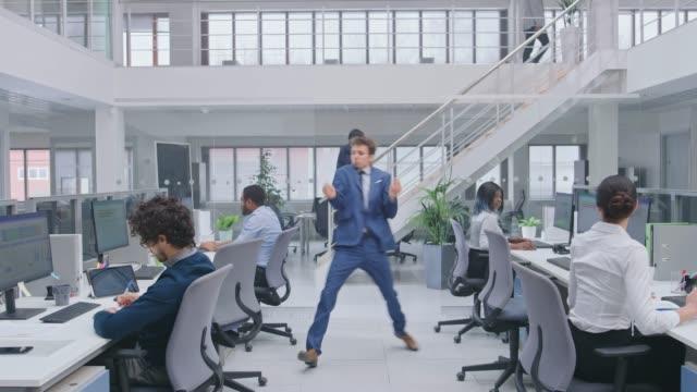 vídeos y material grabado en eventos de stock de joven alegre guapo gerente de negocios usando un traje y corbata bailando en la oficina. la gente de negocios diversa y motivada trabaja en las computadoras en la oficina abierta moderna. - corbata