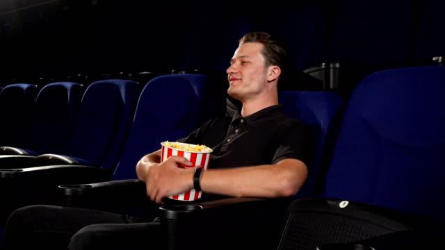 vídeos de stock, filmes e b-roll de jovem homem bonito alegre convidando você para se juntar a ele no cinema - balde pipoca