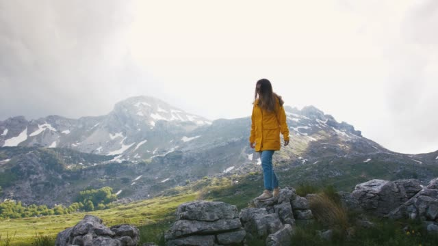 Young cheerful woman in a yellow raincoat walking on rocks with beautiful mountains background, slow motion