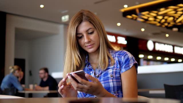 Young Cheerful Woman In Blue Checkered Shirt Sits In Cafe Uses Smartphone video