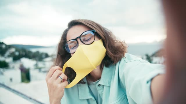 young cheerful woman in glasses and bright yellow face mask taking a selfie - {{relatedsearchurl(carousel.phrase)}} video stock e b–roll