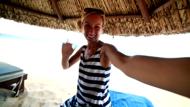 Young cheerful woman taking a selfie on the beach video