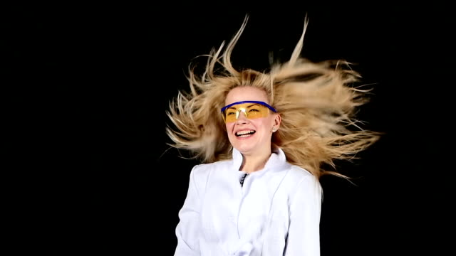 Young chemist blond hair dryer dries hair super on black. Slow motion video