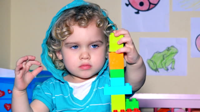 young child girl builds tower with connecting plastic block blocks bricks - 2 3 anni video stock e b–roll