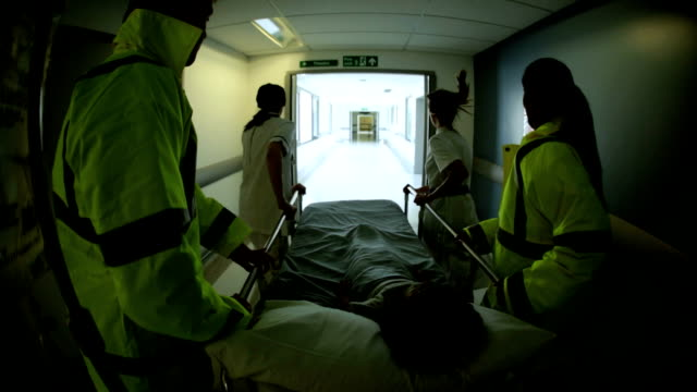 Young Child Rushed Hospital Accident Emergency Wide Angle Wide angle view medical staff paramedics high visibility jackets pushing child patient hospital bed accident and emergency  wide angle stock videos & royalty-free footage