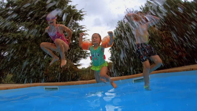 Young children jump into a swimming pool on vacation in slow motion video