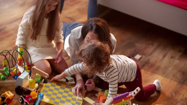 Young children playing messily with their mother on the floor video