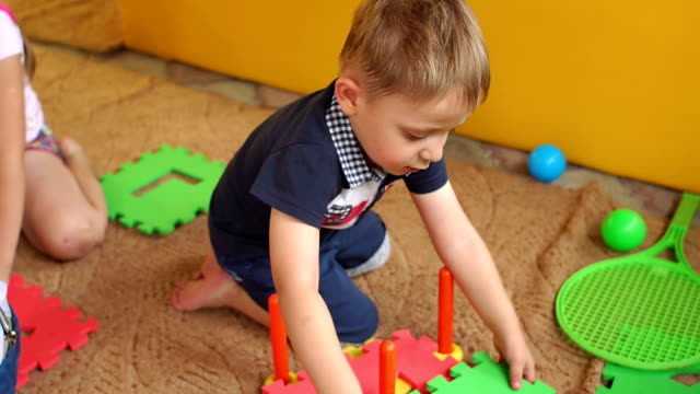 Young children playing with a large soft puzzle. video