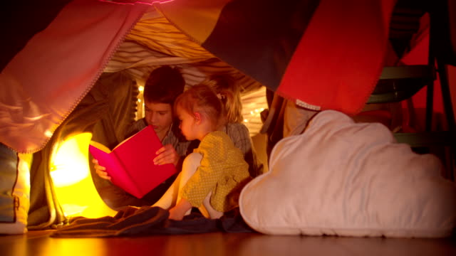Young children reading a night story in their blanket fort video