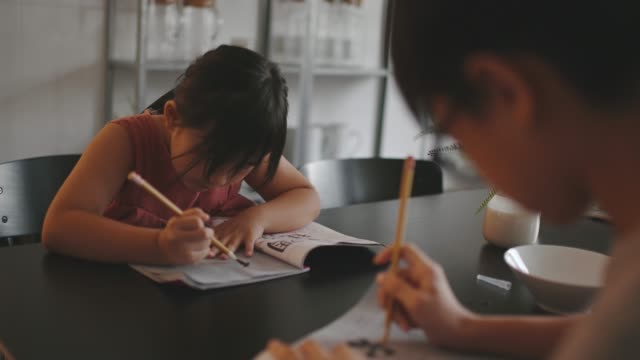 2 young children studying at home writing Chinese calligraphy in dining room