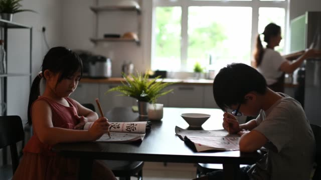 2 young children studying at home writing Chinese calligraphy in dining room while their mother preparing food at kitchen counter