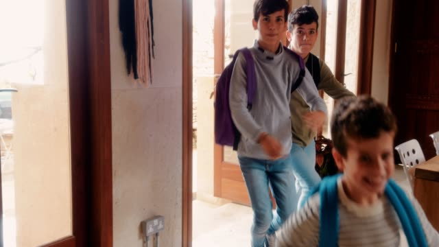 young children with school bags returning home from school - arrivo video stock e b–roll